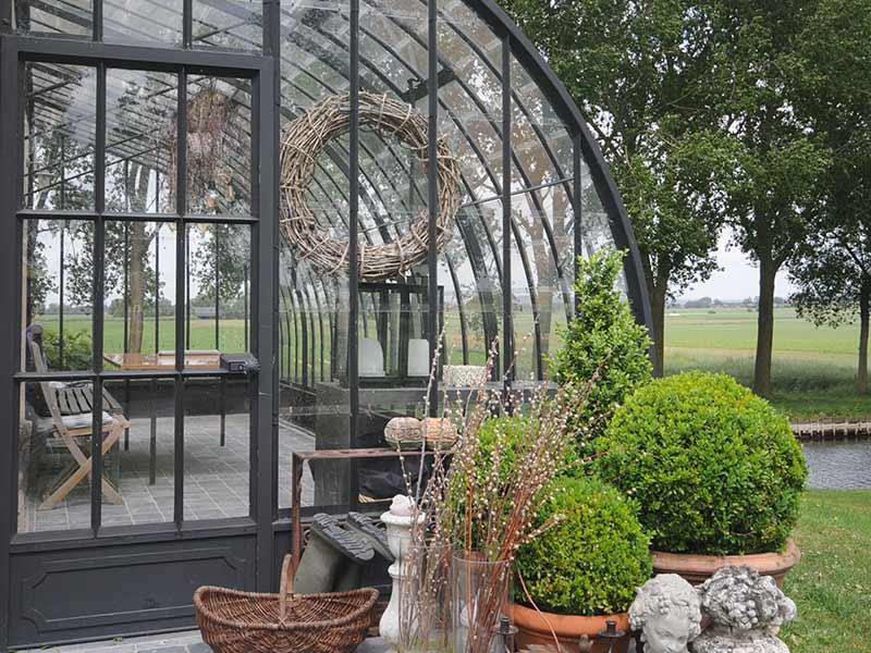 deur en toegang tot serre veranda versierd met decoratie en buxusplanten