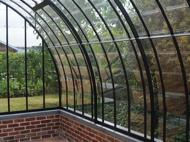 aanbouwveranda in smeedijzer en glas gebogen dak op muurtje met deksteen uit natuursteen dbg classics