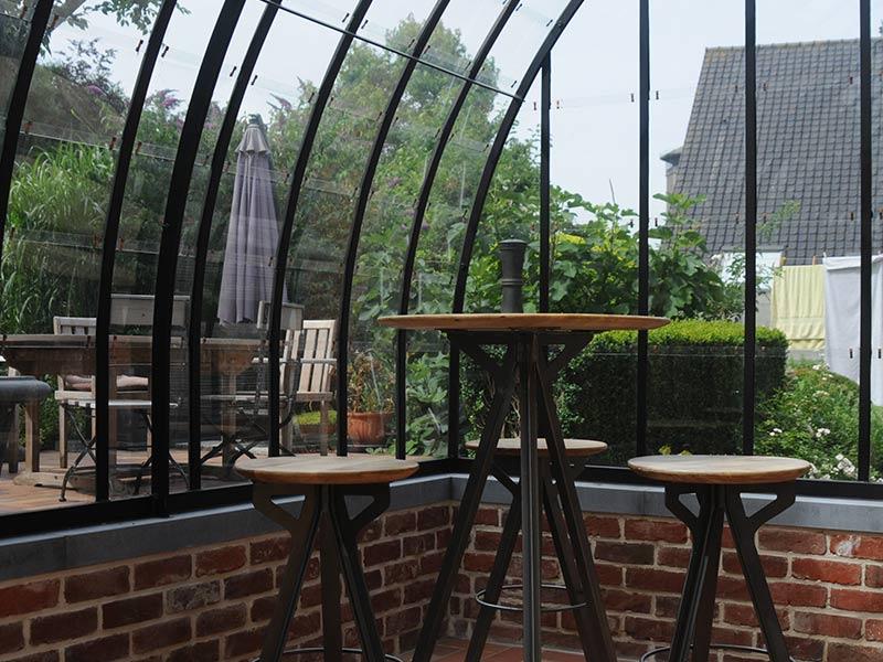 gezellige bartafel met barstoelen in de smeedijzeren veranda van dbg classics