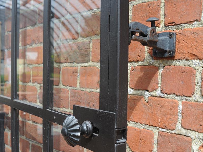 smeedijzeren deur van veranda vastgeklikt aan muur open stand