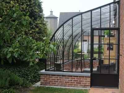 véranda en fer forgé toit en arc de cercle allure orangerie style classique