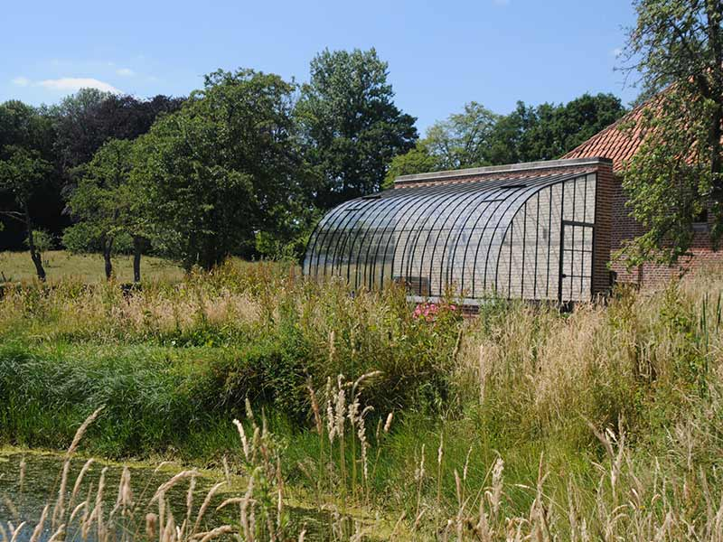 glass lean to greenhouse surrounded by nature and pond dbg classics