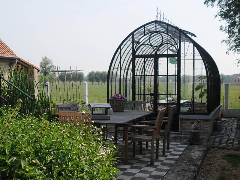 Élégante serre ancienne en fer forgé comme coin repos dans votre jardin