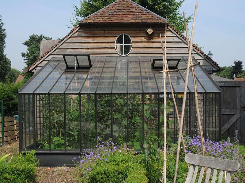 Serre de jardin murale en fer forgé adossée à une annexe dans le jardin