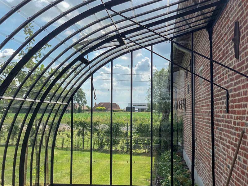 greenhouse against wall curved profiles of roof with additional support for roof connected to brick wall