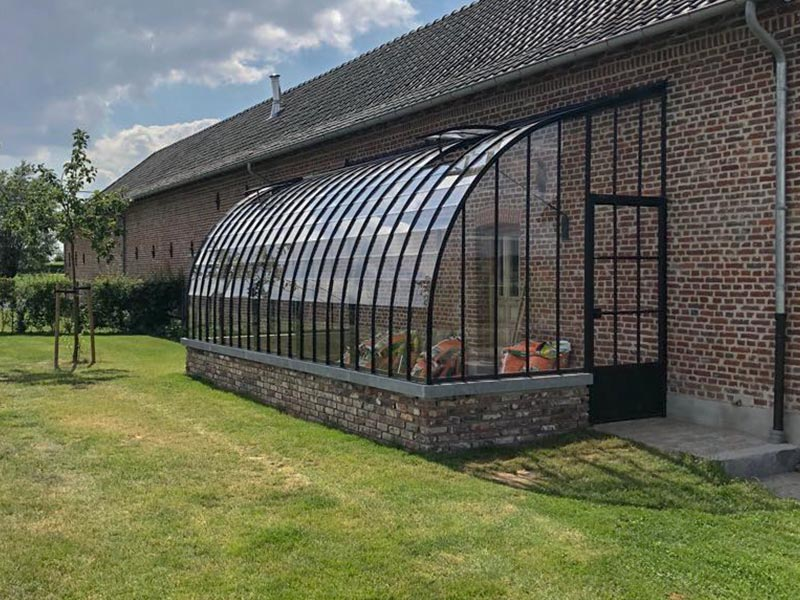 greenhouse against wall wrought iron curved profiles on dwarf brick wall
