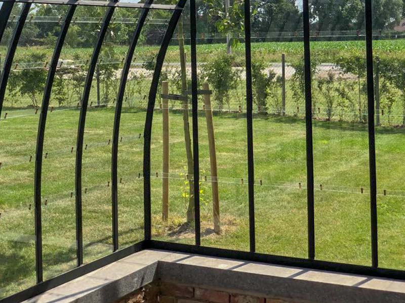profiles of greenhouse against wall built on dwarf brick wall with natural stone on top