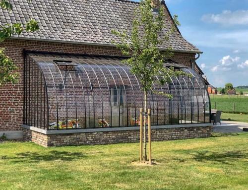 Serre contre un mur en verre et fer forgé avec toit en arc de cercle