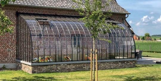 serre contre un mur avec toit incurve en arc de cercle en verre et fer forge