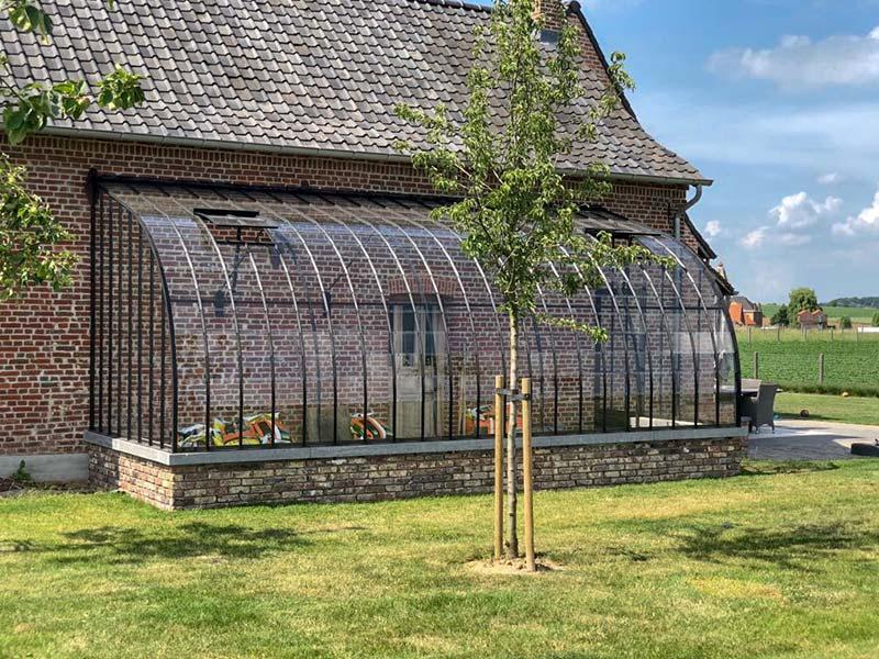 serre tegen muur met gebogen halfrond dak uit smeedijzer en glas
