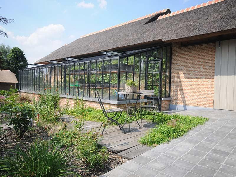 strakke aanbouwserre als smeedijzeren tuindecoratie ideaal voor tuiniers en serrekwekers