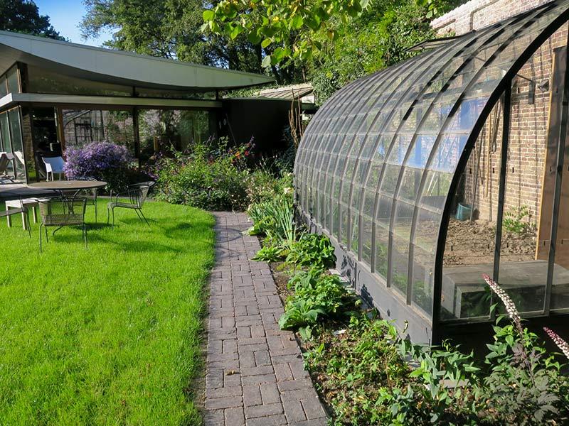 stalen serre aanbouw tegen gemetselde muur in tuin dbg classics