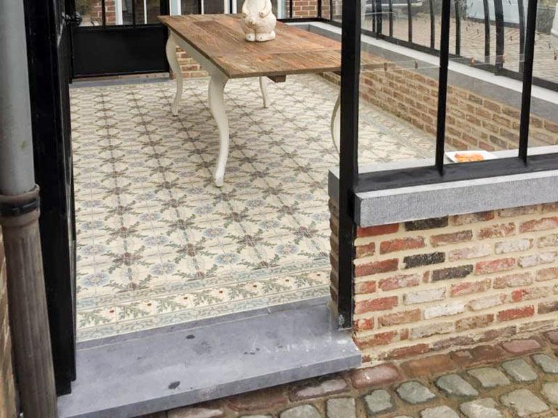 beau carrelage au sol et table agreable sous le toit en verre de la veranda orangerie dbg classics