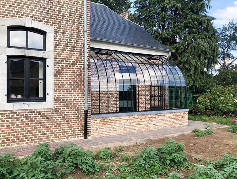 aangebouwde tuinkamer met golvend dak strak design op laag muurtje dbg classics