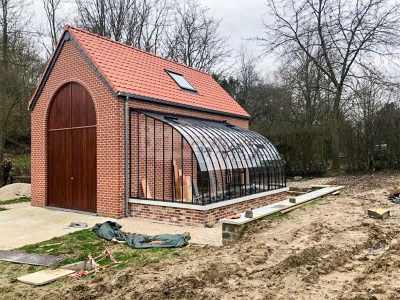 serre rustique classique attenante sur muret avec toit incurve en profils en fer forge