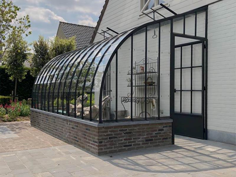 veranda op halfhoog muurtje met golvend dak prachtig aanbouwmodel op terras langs zijgevel woning
