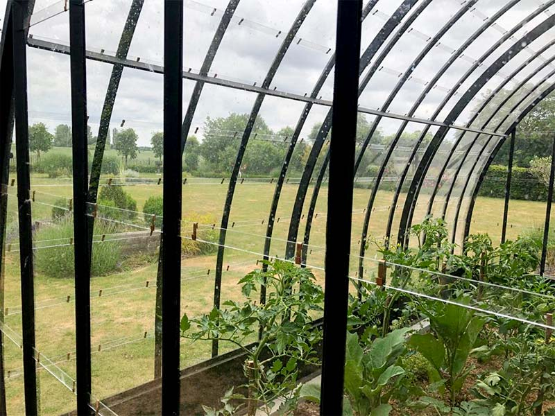 beautiful semi circular greenhouse with curved roof and nice view over the garden dbg classics