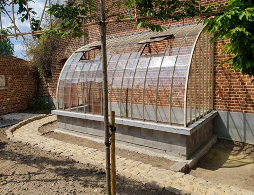 Curved lean-to greenhouse in beige and brown colours in line with the brick wall