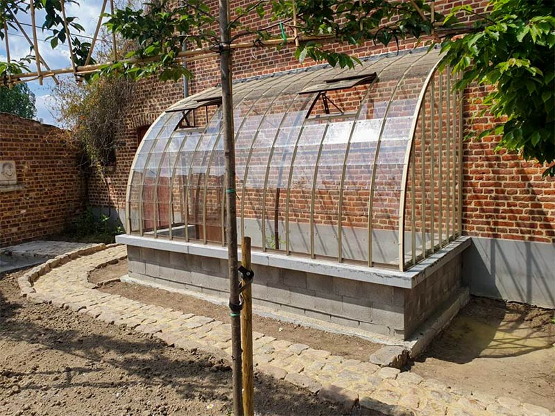 curved lean to greenhouse in beige and brown colours in line with brick wall dbg classics