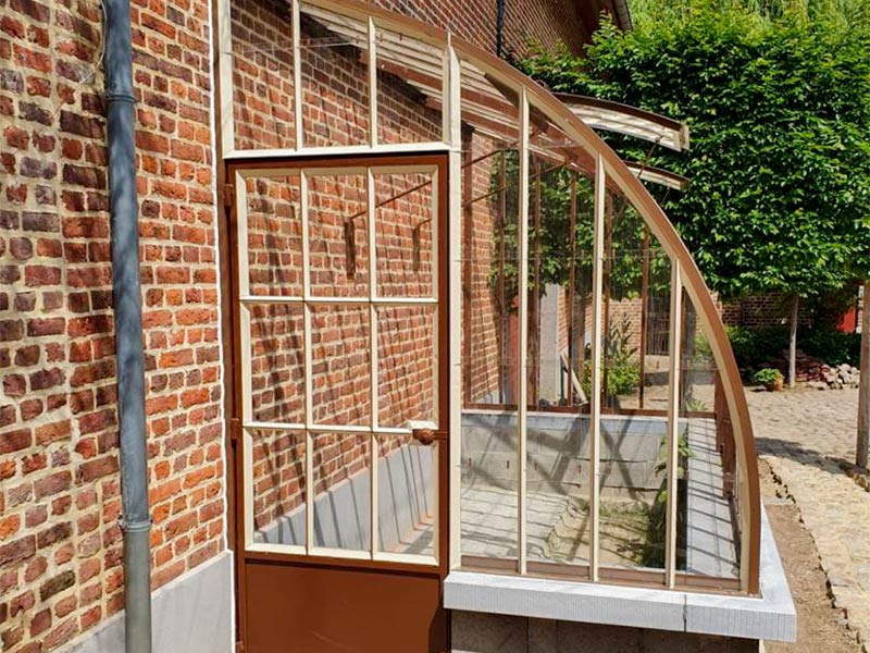 door and entrance of curved lean to greenhouse brown colour with beige silicone finish beautiful combination with brick wall