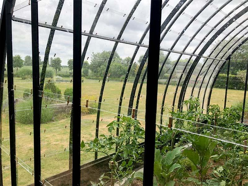 prachtige halfronde serre met gebogen dak uitkijk op tuin en uitgestrekt gazon dbg classics