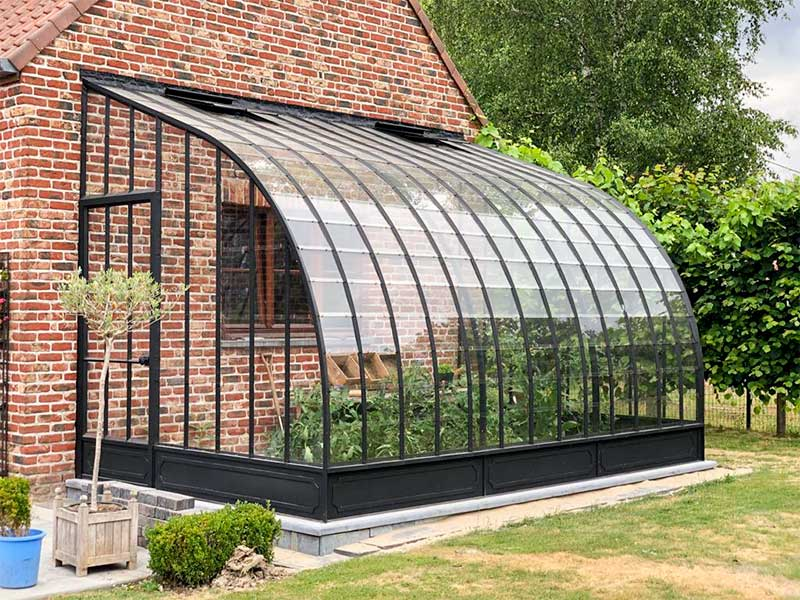 semi circular greenhouse in wrought iron and glass against facade dbg classics