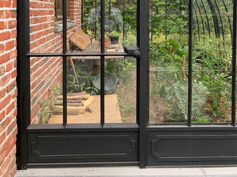 semi circular greenhouse without dwarf wall but with elegant wrought iron raised edge resting on bluestone