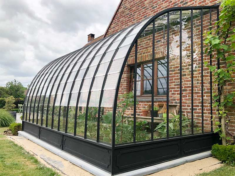 wrought iron curved greenhouse against facade with tomato plants and lettuce inside dbg classics