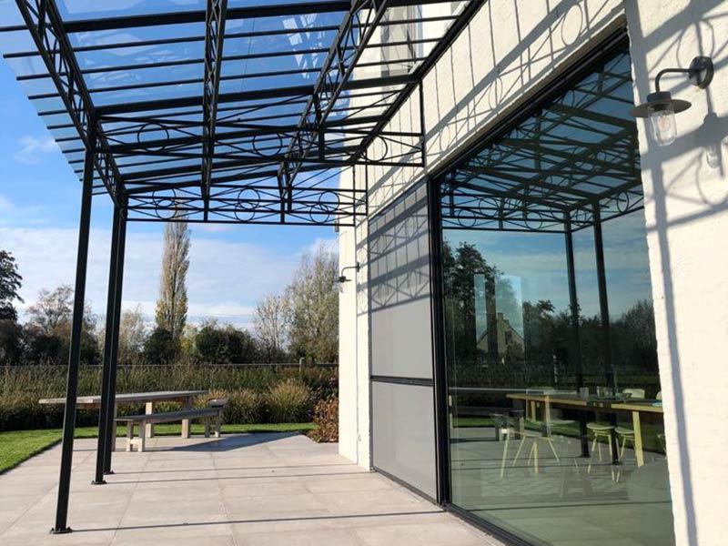 glazen overkapping terras met sierlijke smeedijzeren elementen