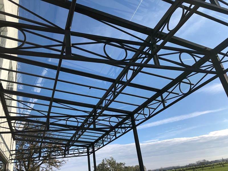 sierlijke terrasoverkapping met dak uit glas en smeedijzeren profielen
