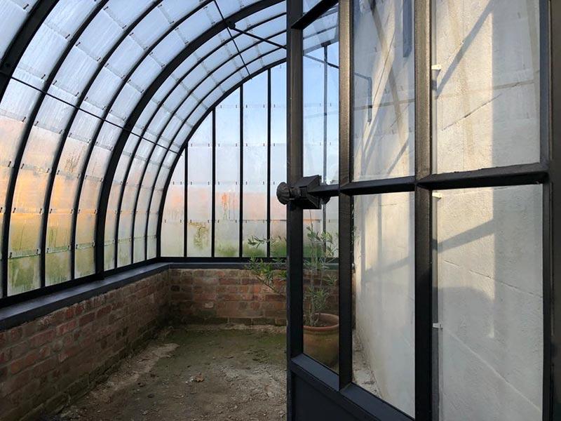 binnenkant stijlvolle serre gebogen smeedijzeren dak witte muur dbg classics