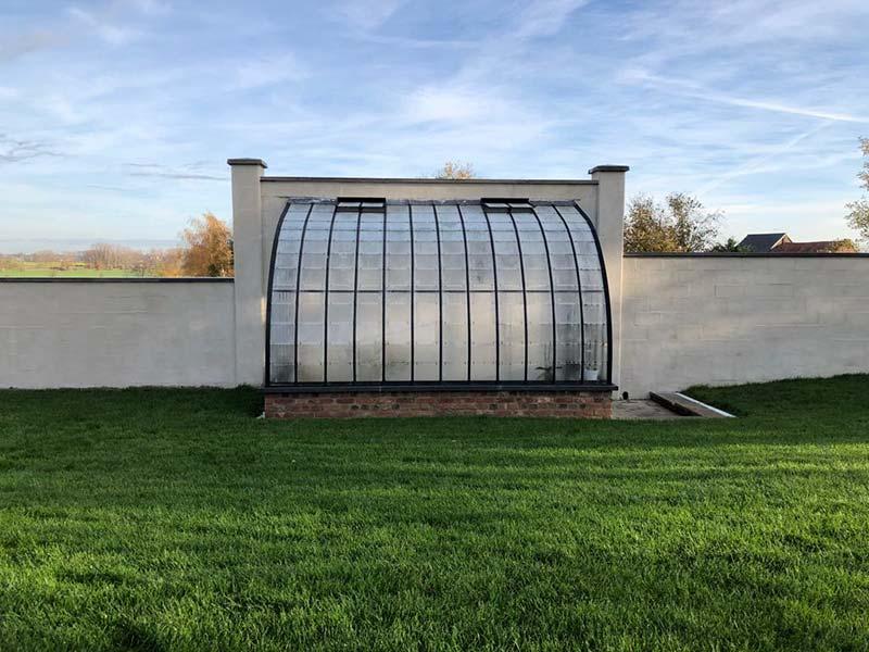 elegante serre aanbouw tegen witte tuinmuur smeedijzer en glas dbg classics