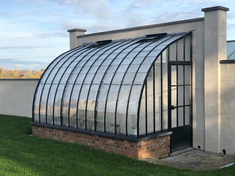 gebogen smeedijzeren dak elegante tuinserre aanbouw model op laag gemetseld muurtje