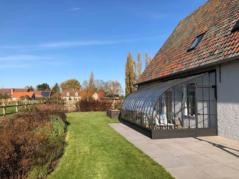 luxe aanbouw serre zwart smeedijzer en glas gebogen dak klassieke uitstraling in landelijke omgeving dbg classics