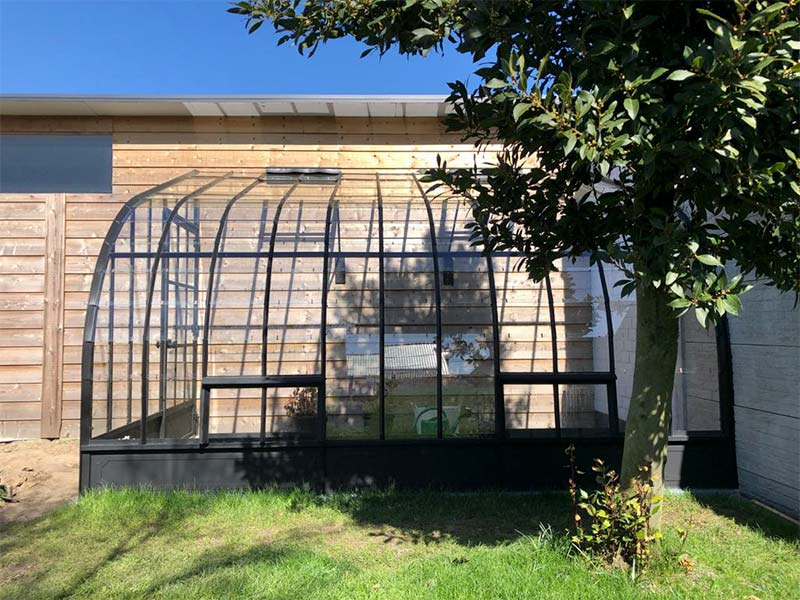 hoek aanbouwserre golvend dak en ingang uit sierlijk smeedijzer en glas