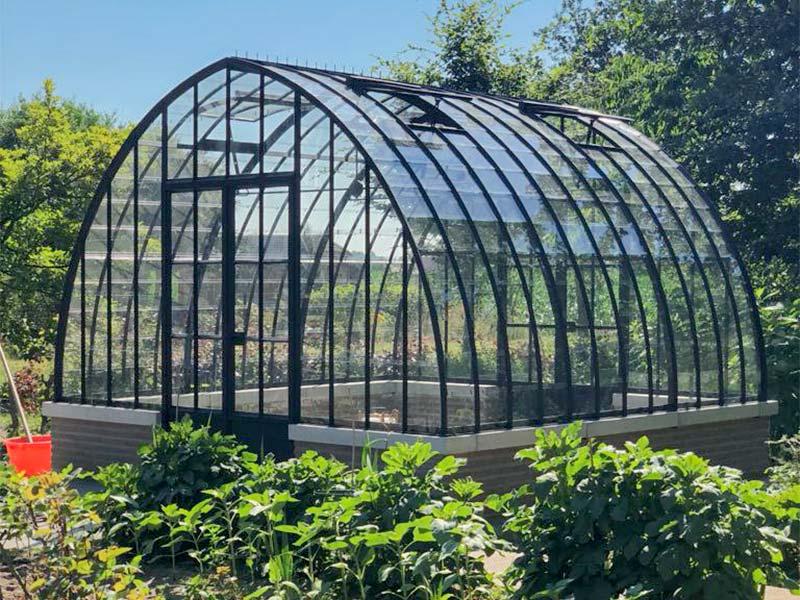orangerie dans jardin construite sur un mur à mi-hauteur avec un toit recourbé dbg classics