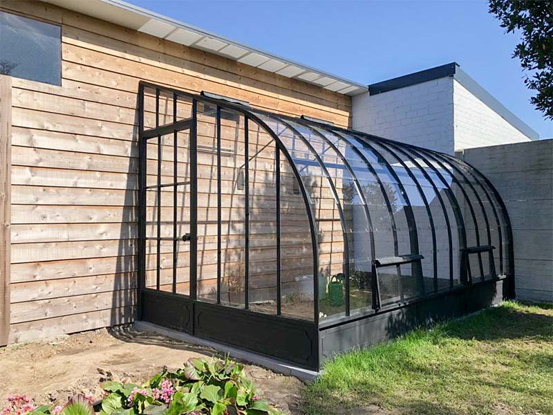 Serre angulaire construite contre deux murs avec volets de ventilation supplémentaires à l'avant