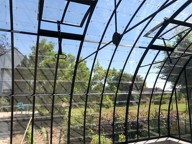 serre courbée modèle indépendant fer forgé et verre look nostalgique accroche l'œil dans le jardin dbg classics