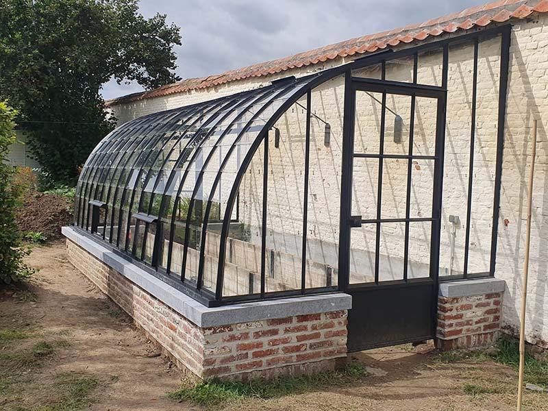 serre de style campagnard construction sur muret avec toit courbé en fer forgé dbg classics