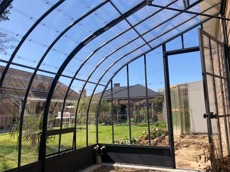 zicht vanuit de hoekserre op de tuin fijne zwarte profielen stijlvol design