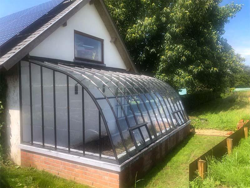 Aangebouwde serre in smeedwerk en glas in achtertuin