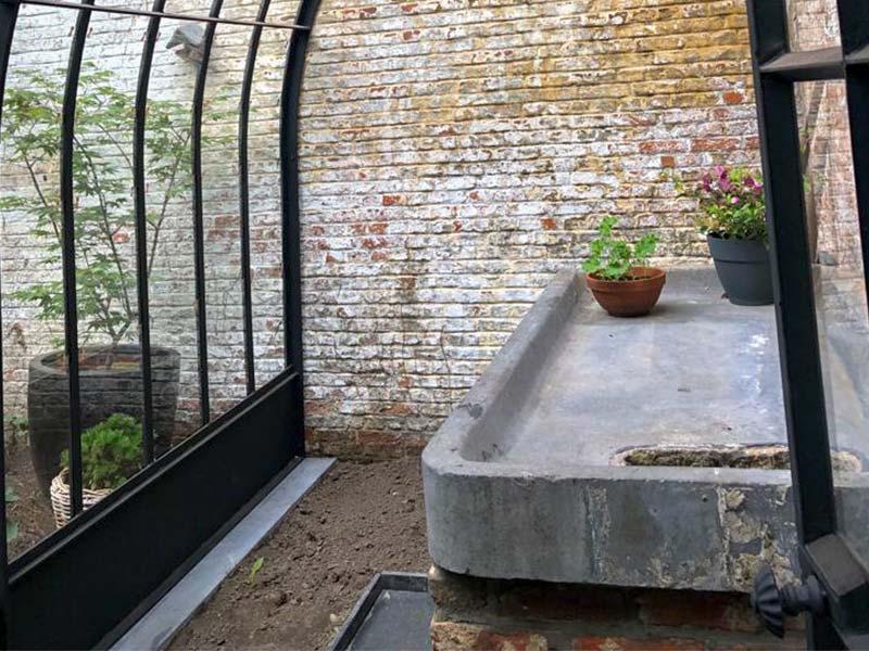 binnenkant serre aanbouw uit glas en smeedijzer verhoogd werkblad natuursteen