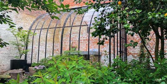 glazen serre aanbouw in hoek in binnentuin stadstuinieren