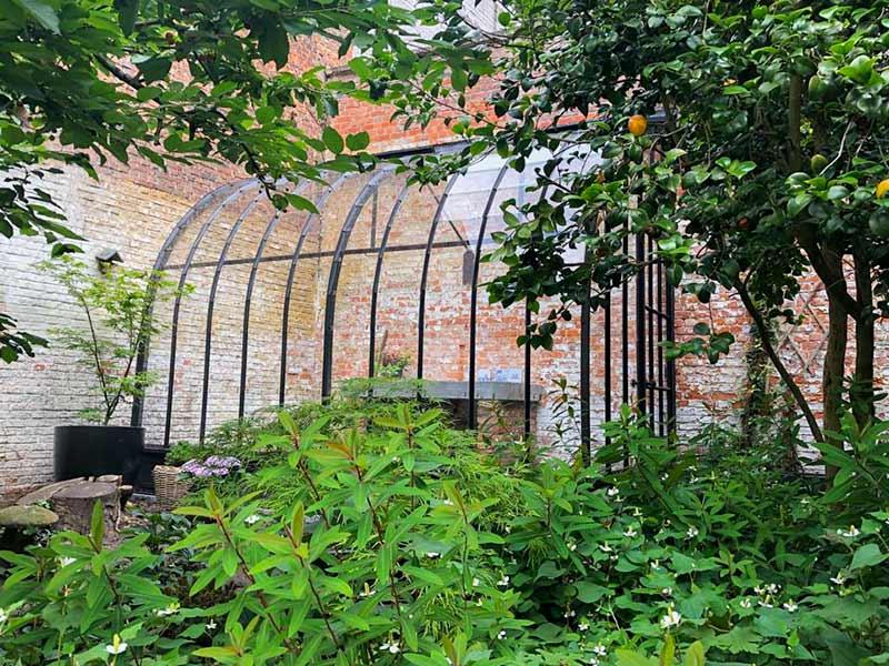 Glazen serre aanbouw in hoek in binnentuin