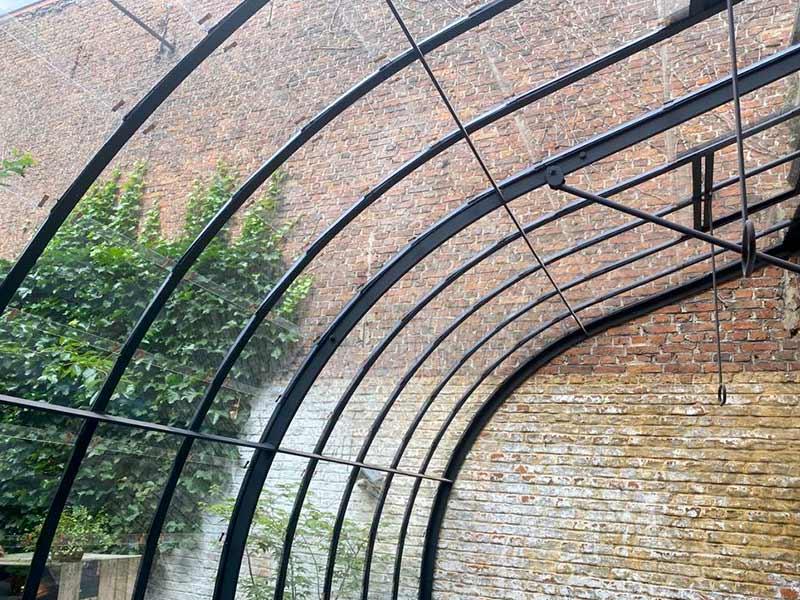 golvend dak van smeedijzeren serre hoekmodel tegen 2 muren