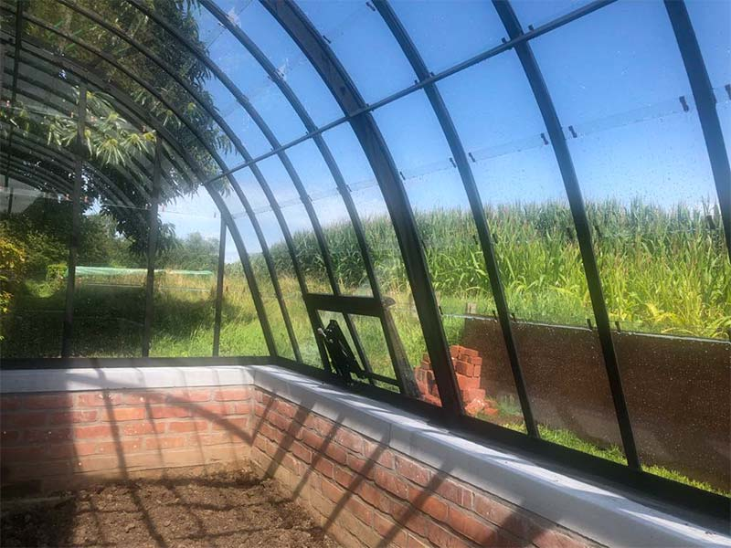 golvende dakprofielen van aanbouwserre die op gemetseld muurtje met natuursteen rusten
