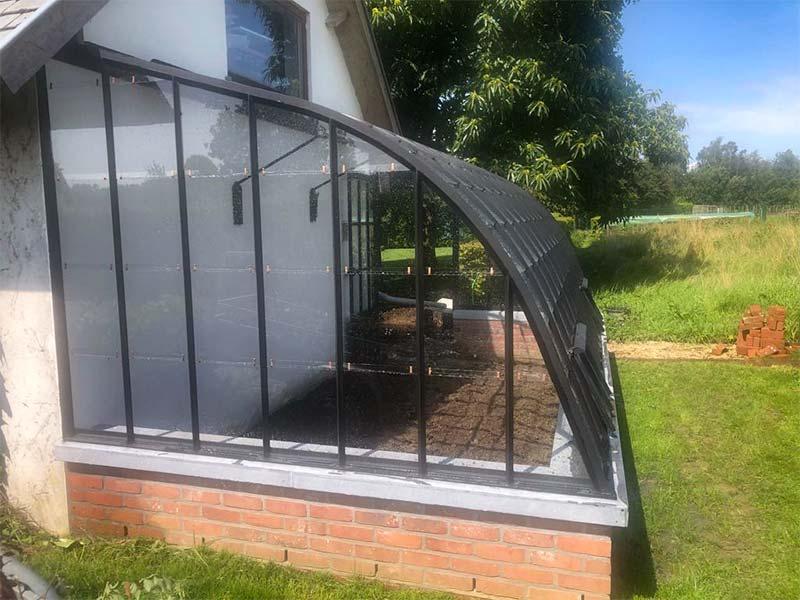 zijkant aangebouwde serre op laag muurtje in achtertuin op zonnige plek